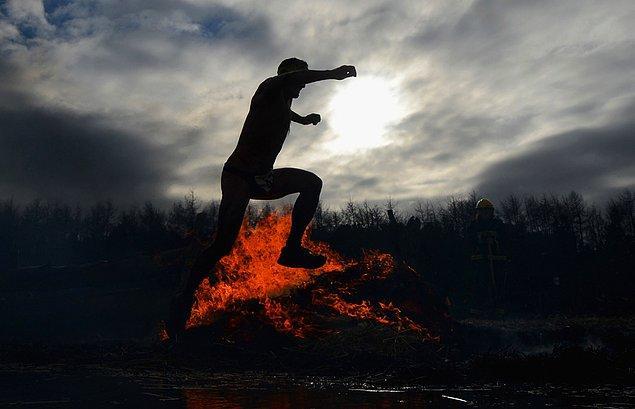13. Ateşlerle boğuşan, ateşin üzerinden atlayan bir yarışmacı.