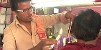 Индийский парикмахер, стрегущий волосы с помощью... свечки