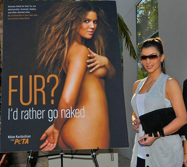 20. Kim Kardashian kız kardeşinin yer aldığı Peta afişinin yanında poz verirken.