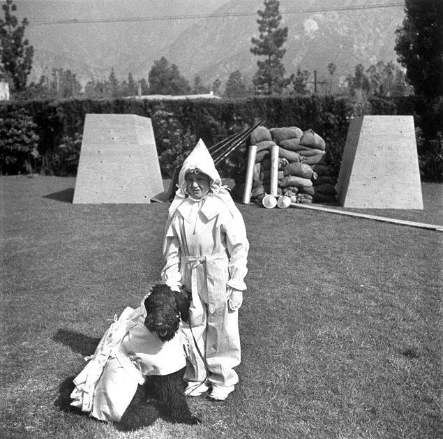 15. Sığınaklarının önünde, en yeni atomik korunma kıyafetlerini deneyen çocuk ve köpeği.