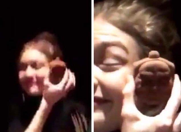 Videoda Gigi, Buddha şeklinde bir kurabiyeyi alıyor ve gözlerini kısarak arkadaşlarıyla gülüşüyor.