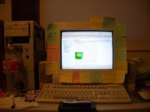 14. Odasında duran üstü post-itlerle kaplanmış bir bilgisayar