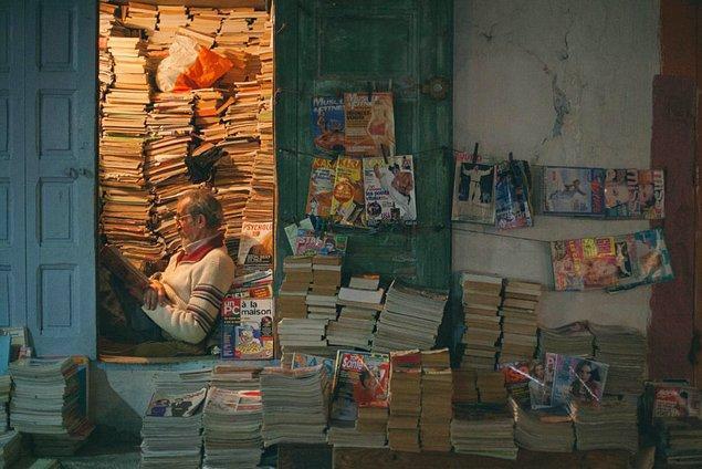 Fotoğraf burada. Hafif yaşlı bir bey kitapları bir odaya özenle dizmiş. Önünde de bir takım mecmualar var.