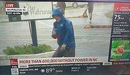 Журналист притворяется, будто бы он противостоит сильному ветру от урагана «Флоренс»