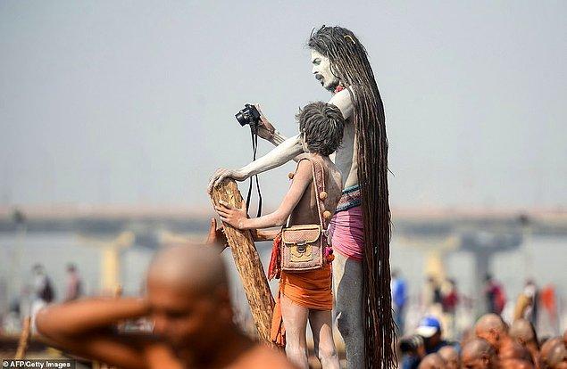 Bir Naga Sadhus, üyeliğe yeni kabul edilen Naga Sadhuslar Ganj Nehri'nde ritüeller gerçekleştirirken fotoğraflarını çekiyor.