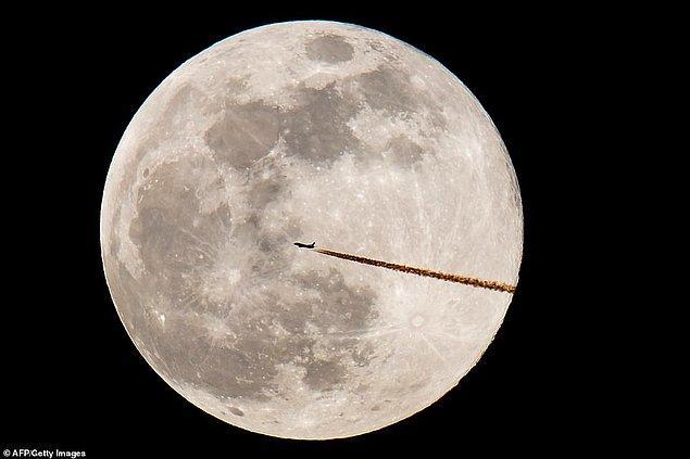 1. Bir uçak silüeti ve Süper Ay'ın, Almanya'nın Nürnberg şehrinden bir görüntüsü.