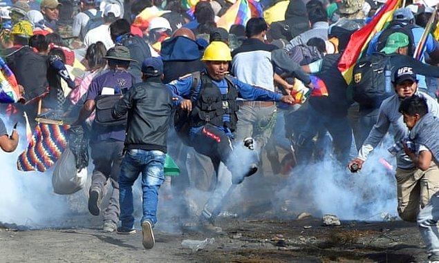 Sacaba'daki koka yetiştiricileri ve eski başkan Evo Morales'in destekçileri, polisin attığı göz yaşartıcı gazlardan kaçıyor.