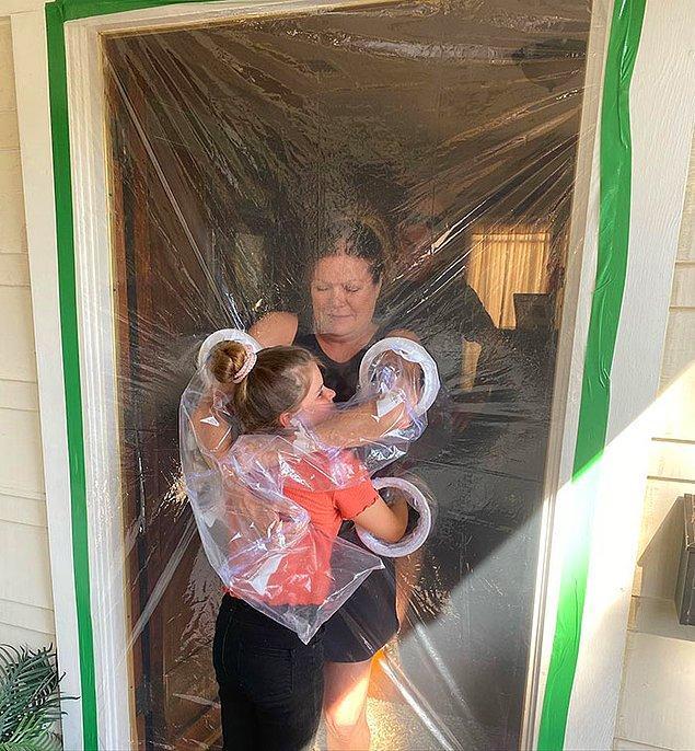 Büyükanne ve büyükbabasına sarılabilmek için küçük kız, bu plastikten yapılan ve kol bölmeleri olan perdeyi tasarladı.