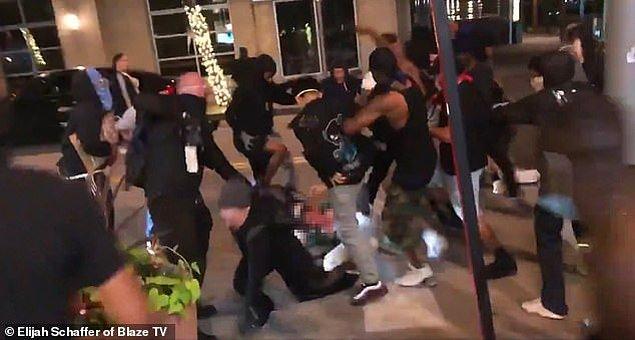 Bir protestocuyu kovalayan adam daha sonra ökfeli kalabalık tarafından acımasızca dövülüyor.