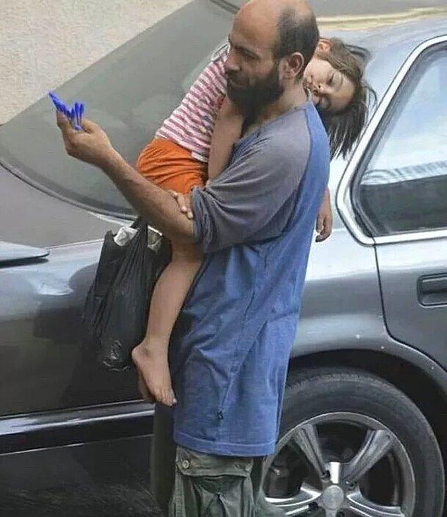 1. Suriyeli mülteci olan Abdu, kızını kucağında tutarak kalem satıyor...