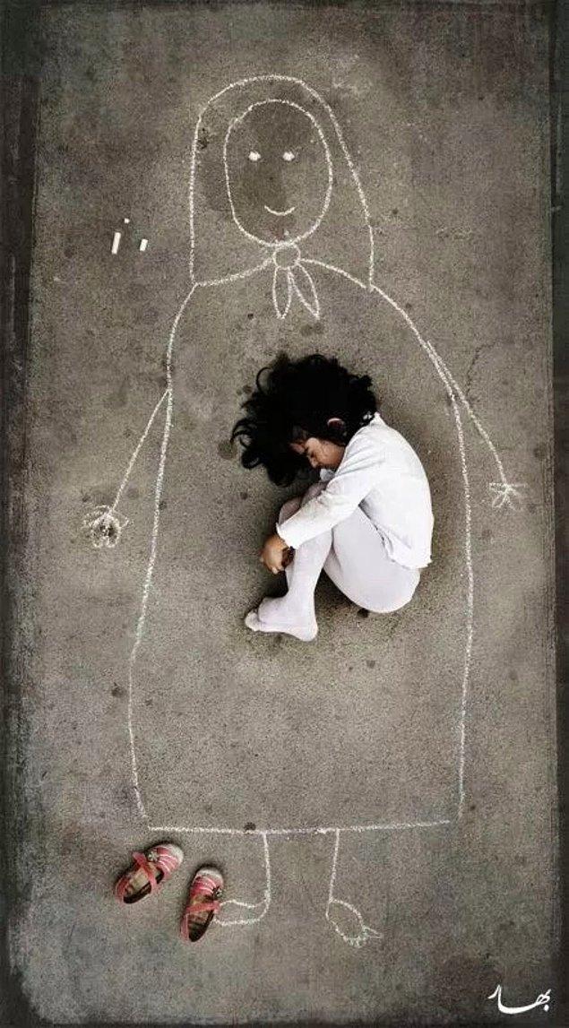 8. Irak'taki bir yetimhanede yaşayan küçük bir kız çocuğu yere anne resmi çizerek üzerinde yatıyor.