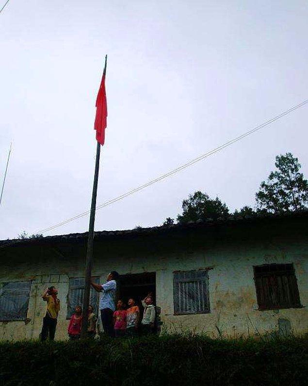 10. Yardıma muhtaç bölgelerde 12 yıl boyunca çalışan Çinli öğretmen Li Shunxiang ve 7 öğrencisi, yeni öğretim yılı için bayraklarını çekiyorlar.