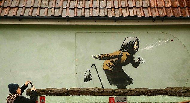 Kimliği belirlenemeyen sanatçı, İngiltere'nin Bristol kentinde bir evin duvarına hapşırırken takma dişleri ağzından fırlayan bir kadın çizdi.