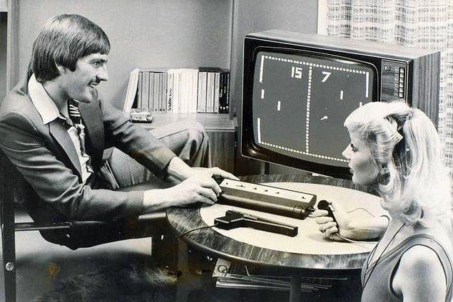 1. Dönemim ünlü Liverpool FC oyuncusu Steve Heighway bir kadınla birlikte  Videomaster oyun konsolunda Pong oynuyor. -1977