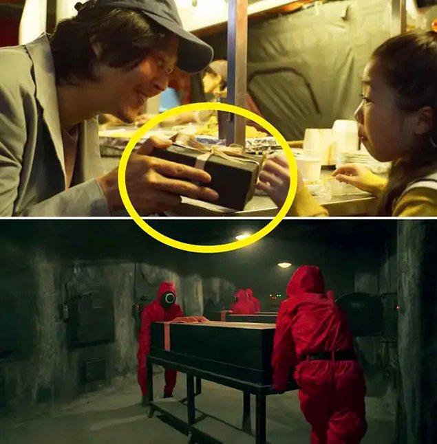1. Oyuncuların öldükten sonra içinde taşındıkları kutular, Gi-hun'un kızına aldığı hediyenin koyulduğu kutuya benziyor.